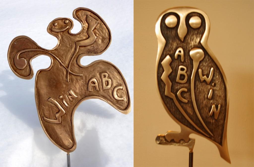 trophées en bronzes représentant un bonhomme joyeux et une chouette.