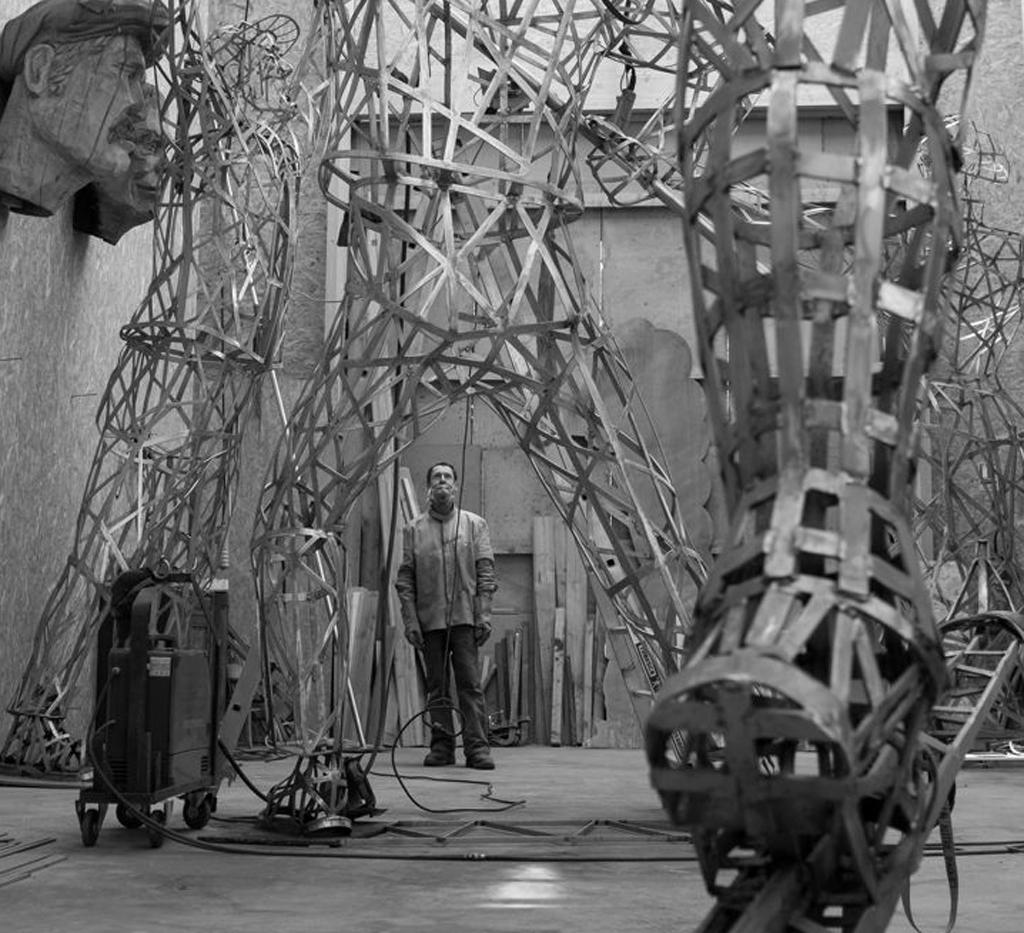 photo du sculpteur Christian Burger entouré de ces sculptures en acier inoxydable.