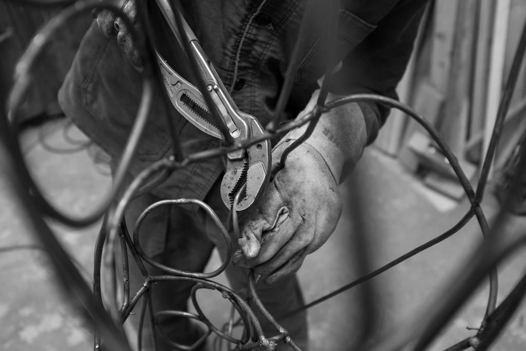 photo des mains du sculpteur tordant et assemblant les anneaux en acier pour la sculpture