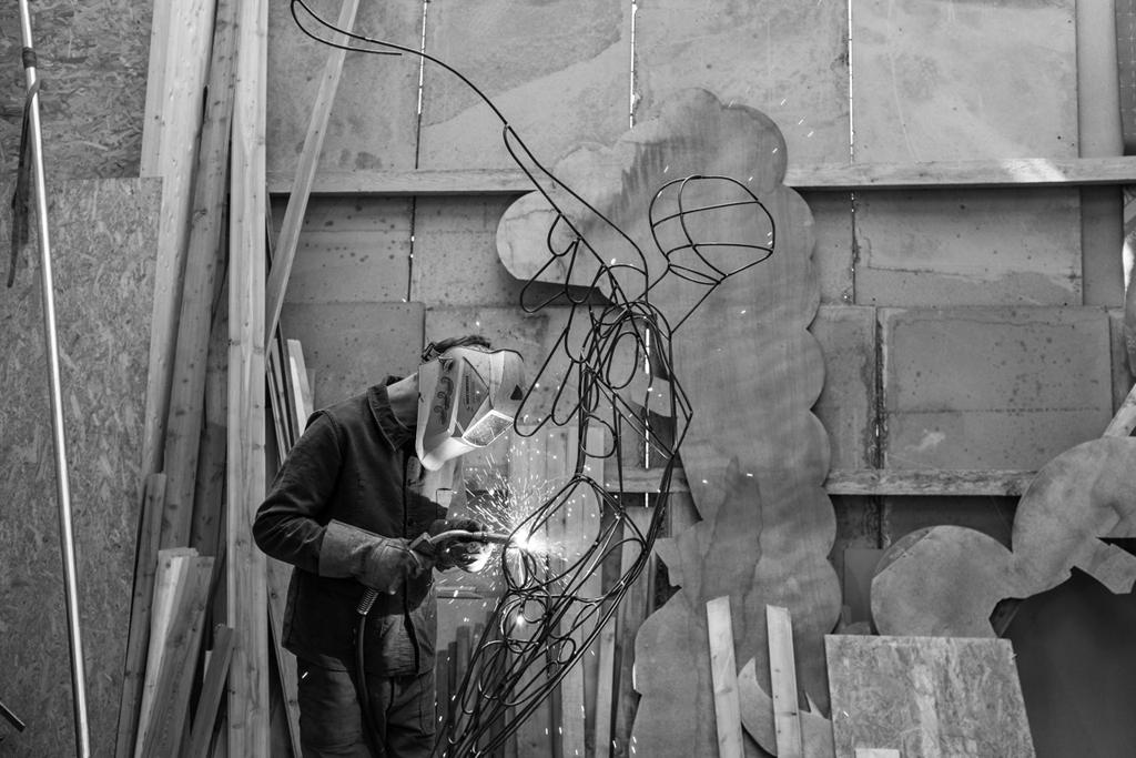 photo du sculpteur assemblant les anneaux en acier pour la sculpture