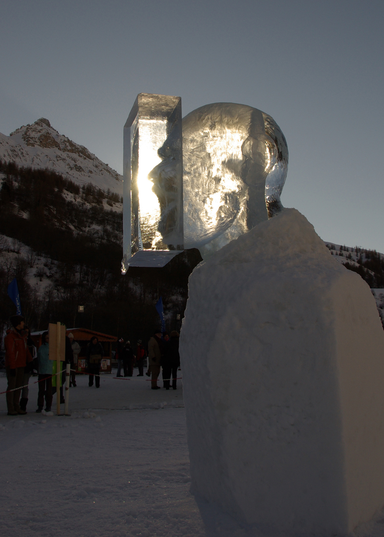 photo de la sculpture sur glace représentant une tête d'homme qui crie, son visage est pris dans un bloc de glace, mais on le voit par transparence. L'on peut voir le visage deux ou trois fois par reflet sur les différentes faces du cube. Ici un jeu de lumière s'opère qui donne l'impression que le son du cri reste coincé dans le cube.