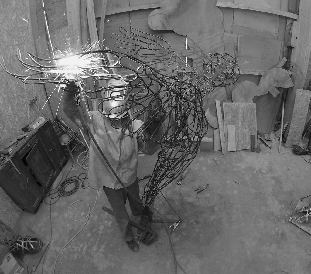 """photo de christian burger soudant sur la sculpture en acier """"Envol"""""""