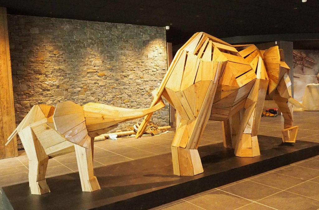 Photo d'un éléphanteau suivant l'éléphant accroché par la queue, sculpture en planche réalisée par christian Burger pour le Club Méditerranée de La Rosière en Savoie, France.