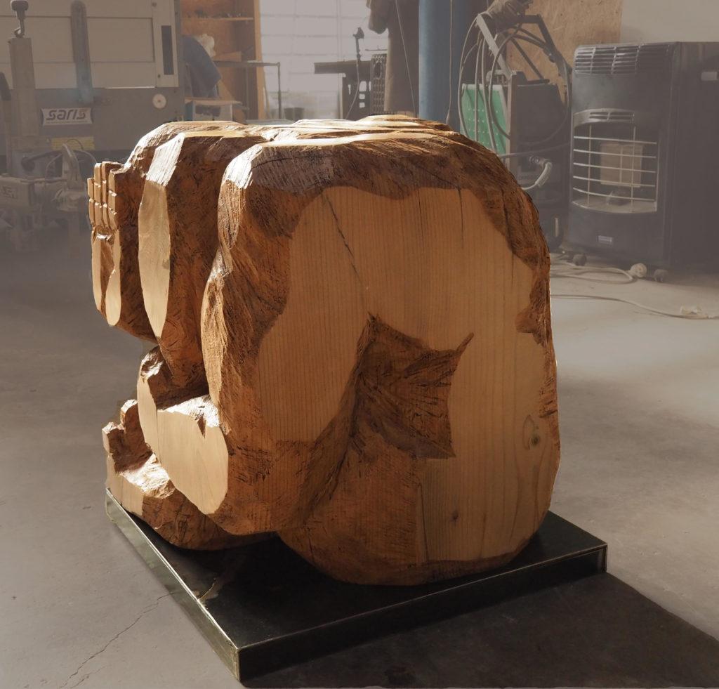 sculpture d'un homme en bois comprimé dans un cube